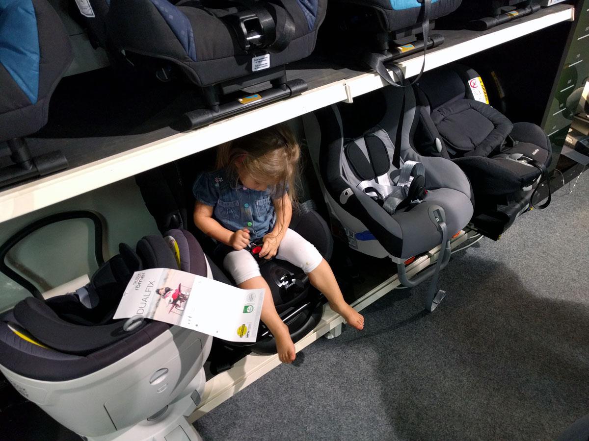 Claire spielt verstecken zwischen Kindersitzen
